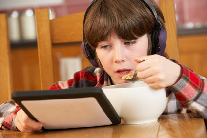 Boy Using Tablet Computer Whilst Eating Breakfast